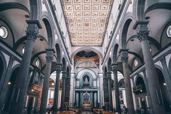 La foto riprende l'interno della basilica di San Lorenzo a Firenze come se la vedessimo stando nella navata centrale. Al lato destro e sinistro due file di alte colonne segnano le navate laterali. Gli archi tra le colonne compongono i moduli quadrati delle campate che definiscono lo spazio in modo ritmico e equilibrato